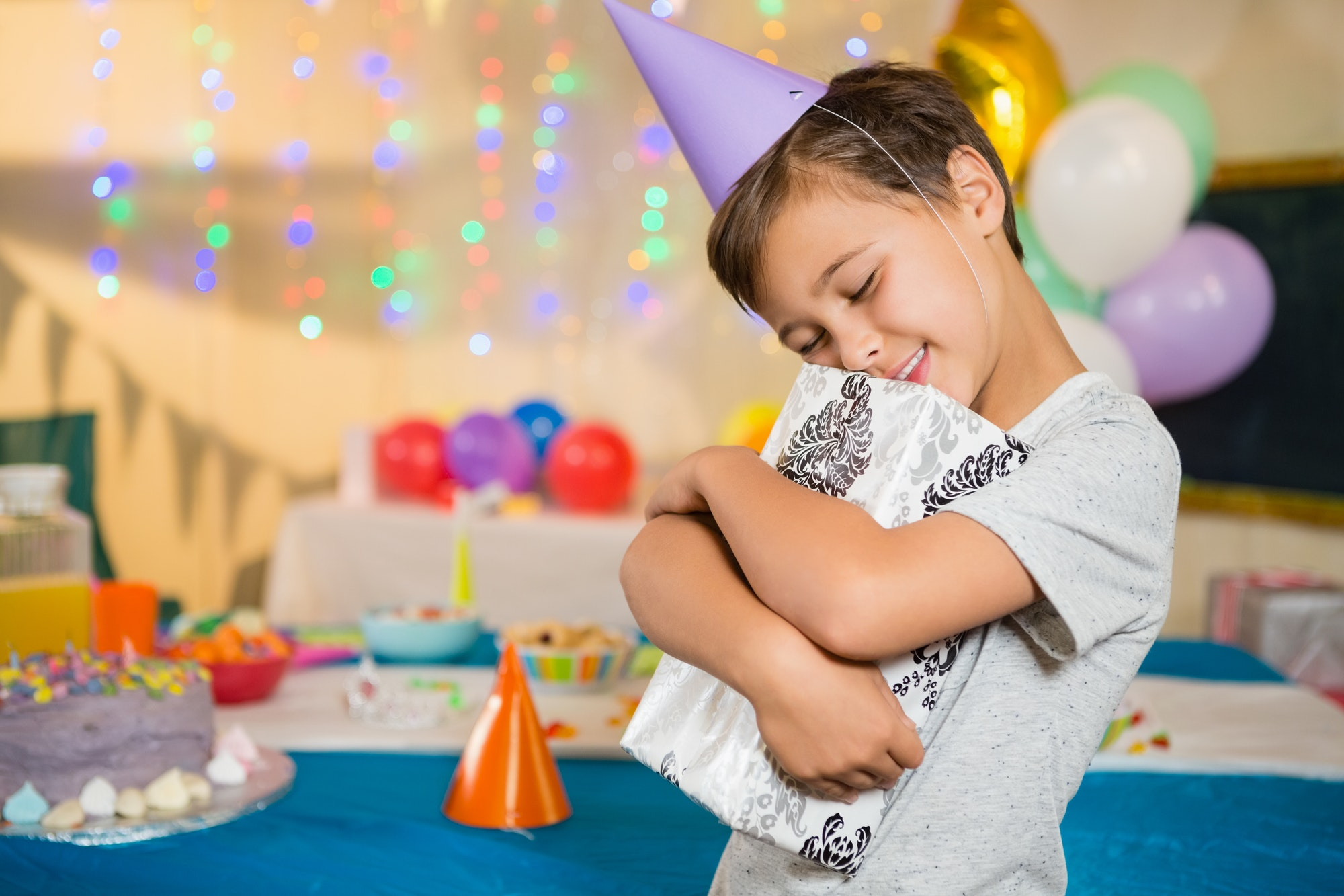 Boy embracing gift box during birthday party