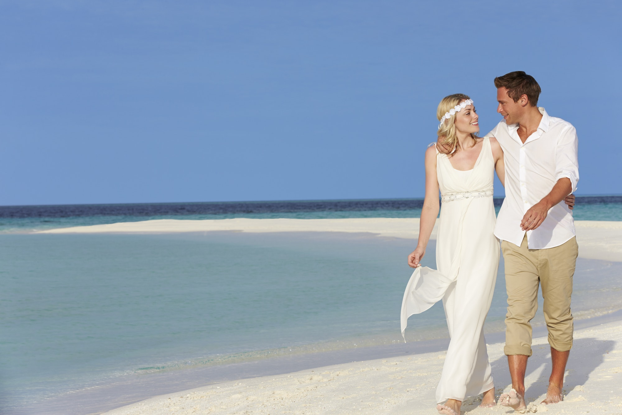 13th wedding anniversary gift ideas - A couple enjoying walking around beachside